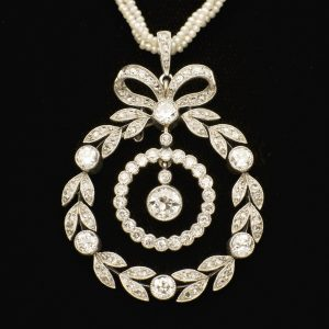 Edwardian diamond pendant designed as a circular wreath and bow