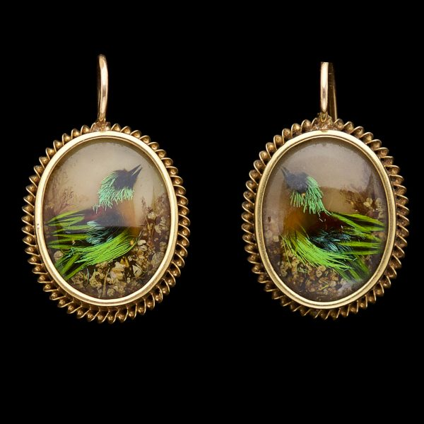 Victorian earrings with a design of birds made of bird feathers against a mother of pearl background