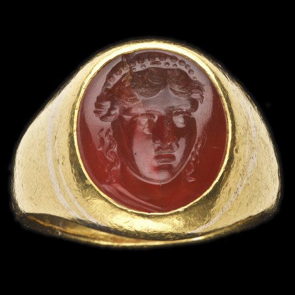 Ancient Roman cornelian intaglio carved with a Maenad, her hair centrally parted and caught up with vine leaves, curly tresses about her face, sprigs of fruit and ribbons around her head. 1st century AD. Set in a later beaten gold setting