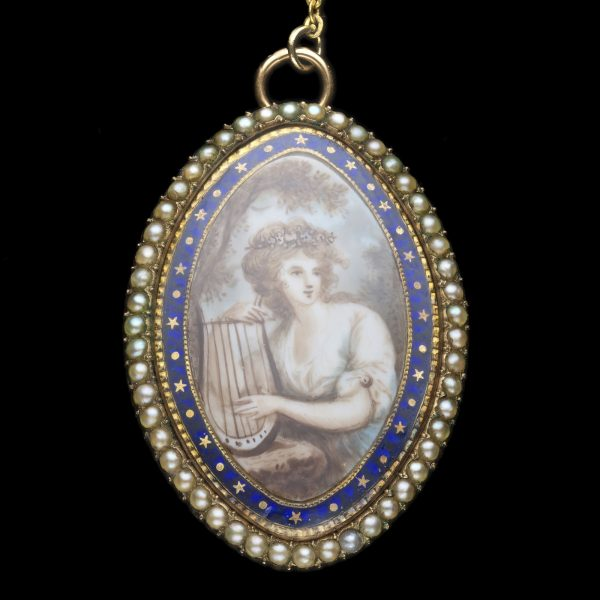 Georgian gold marquise shaped brooch with a miniature painting on ivory of an 18th century woman playing a lyre, within a border of blue enamel and pearls. Hair locket to the reverse. English c.1790's.