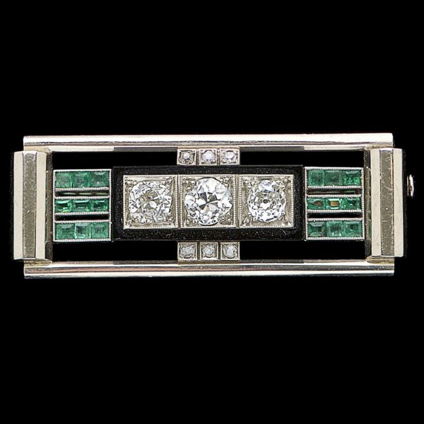 Art Deco platinum, diamond, emerald and onyx brooch. The central panel set with three diamonds 1.34ct H-J colour, within an onyx frame, three rows of small emeralds on either side