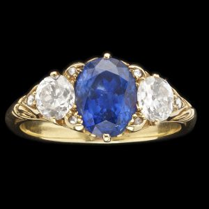 Edwardian sapphire and diamond ring, the sapphire 2.67cts, 2 side diamonds= 0.96cts, G-H colour, in a carved scrolled 18ct yellow gold setting