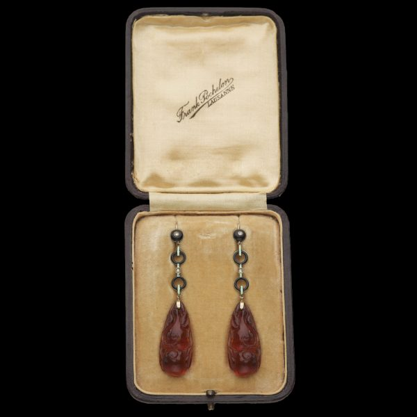 Art Deco carved amber ear pendants, mounted with black enamel hoops with white enamel bars. By Frank Pochelon Lausanne