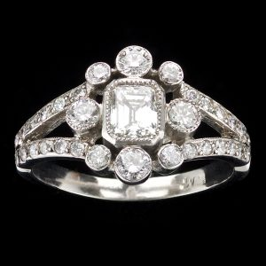 Diamond and platinum cluster ring set with a central emerald cut diamond 0.56ct L-M/VS1 surrounded by small diamonds total 0.76ct