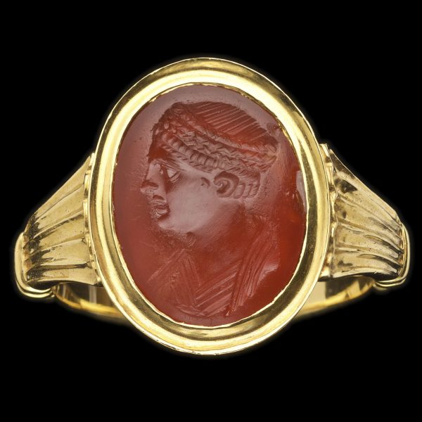 Roman cornelian intaglio, early 2nd cent AD, carved with a draped bust of a woman in profile, her hair in a thick plait wound around her head. Contemorary 22ct gold setting