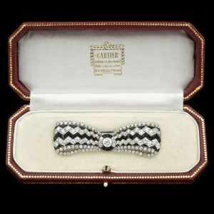 Art Deco onyx and diamond bow brooch in platinum setting marked Cartier c.1930. Original Cartier case