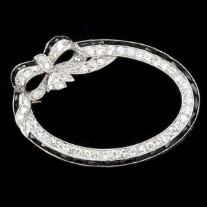 Art Deco oval diamond and onyx ribbon and bow brooch, platinum setting