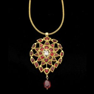 gold pendant kundan set with central flat cut diamond and red spinels