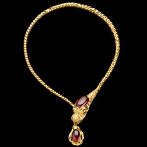 Antique gold articulated chain mythological dragon necklace, the head set with a large oval cabochon garnet, holding in its mouth a gold pendant set with a cabochon garnet. English c. 1870