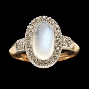 Victorian gold ring set with an oval moonstone surrounded by rose diamonds the shoulders also set with diamonds. Locket section at the back of the moonstone , English c 1960