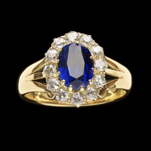 Victorian sapphire and diamond cluster ring, the natural dark blue sapphire surrounded by small brilliant cut diamonds, set in 18ct yellow gold hallmarked Birmingham 1900