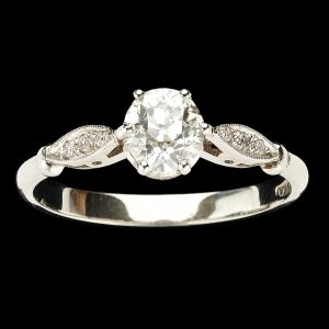 Diamond solitaire ring, the round brilliant cut diamond 0.60ct with diamond set leaf shaped shoulders in a platinum setting