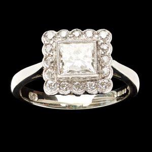 Contemporary platinum ring set with a 1ct square brilliant (princess) cut diamond within a diamond border