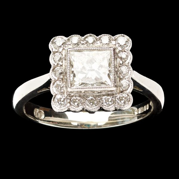 Contemporary platinum ring set with a 1ct square brilliant (princess) cut diamond within a diamond border