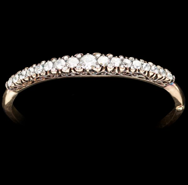 Antique diamond hinged bangle. The diamonds graduate from 0.57ct to 0.10ct. Diamonds total 3.20ct, 15ct carved and scrolled gold setting