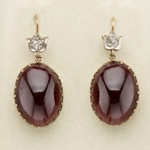 Victorian cabochon garnet earrings, the oval garnets in fine gold, claw settings are suspended from small, rose diamond mounts